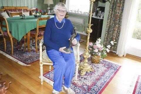 AKTIV: Liv Mustorp i stuen med en lampefot som skal ha tilhørt lord Nelson, og Idrettsmerkestatuetten som hun fikk etter å ha tatt merket 15 ganger. Foto: Terje Vidar Høvik