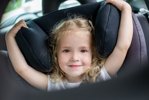 happy kid girl in the car seat