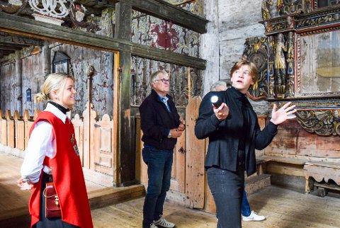 En engasjert guidelærling Even Yngvar Volden forteller om interiøret i stavkirka mens guide Astri Skarvøy følger nøye med.