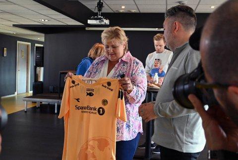 Erna Solberg fikk overrakt en Glimtdrakt av daglig leder i Bodø/Glimt Frode Thomassen.