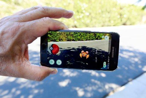Pokémon Go-spillet går ut på å fange figurer som popper opp på mobilskjermen som viser virkelige bilder fra området spilleren befinner seg på. Foto: Scanpix