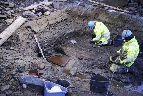 Her ser vi arkeologene fra NIKU avdekke kister fra 1200-tallet dypt nede i gaten foran Domkirken. Arkeologene trodde kistene var tomme, men så oppdaget de tenner som kan kobles til gravene. (Foto: THOMAS WRIGGLESWORTH)