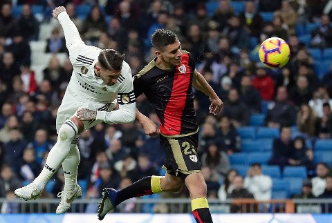 Real Madrid's Sergio Ramos, left, heads for the ball near Rayo Vallecano's Emiliano Vazquez during the Spanish La Liga soccer match between Real Madrid and Rayo Vallecano at the Bernabeu stadium in Madrid, Spain, Saturday, Dec. 15, 2018. (AP Photo/Manu Fernandez)
