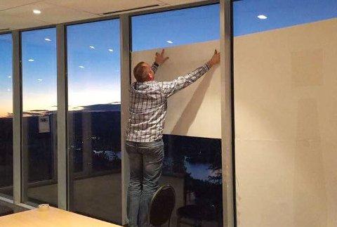 Espen Tangerud henger opp de store plakatene på vinduene i Vingen på toppen av Vikersundbakken.