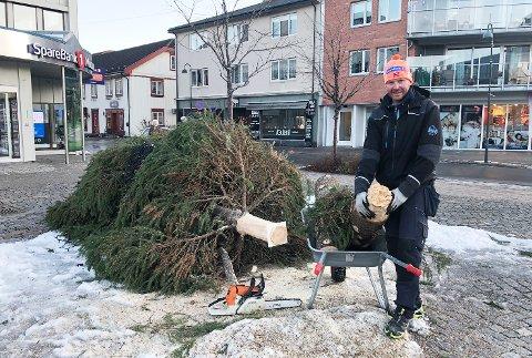 KNAKK: Vaktmester Vidar Moen i Sparebank 1 Modum viser fram stammen på julegrana som knakk tvers av i vindværet tirsdag kveld.