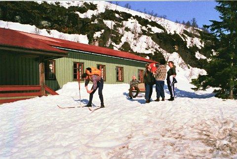 TROLLSTOVA: Klar til avgang. Det er grovkorna snø og klassisk klisterføre, men dei tre damene til høgre ser ikkje ut til å ha nokon hast med å komme avgarde. Mannen på benken er Kristian Furehaug, dåverande formann i BUL sitt hyttestyre.