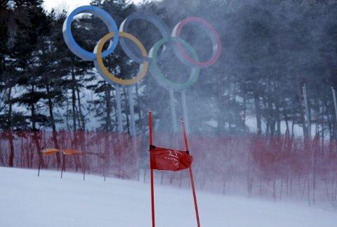KALDT OG VINDFULLT: Vinden gjør det surt og kaldt i Pyeongchang, og det er allerede blitt utsettelser. Vår kommentator mener at IOC aldri må tildele OL til en arrangør som har slike forhold. (AP Photo/Luca Bruno)