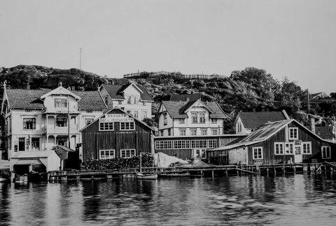 Eikelands Møbelfabrikk på Øya: Dette fotografiet kan fortelle mye. Eikelands Møbelfabrikk er en ting. Men se i første etasje i Westgaards hus til venstre, hvor det var en liten kolonialbutikk tidligere. Bildet er tatt like før, eller like etter krigen. Heia bak husene er ikke bebygd, men det er satt opp et stakittgjerde. Bygningene bak fabrikken kom opp etter den store brannen på Øya i 1900.