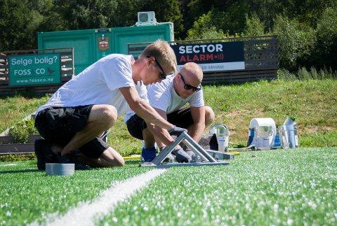 Tauri Kukke (til venstre) og Carl Stefan Turgan fra Greensport legger det nye kunstgresset på Nordby stadion.