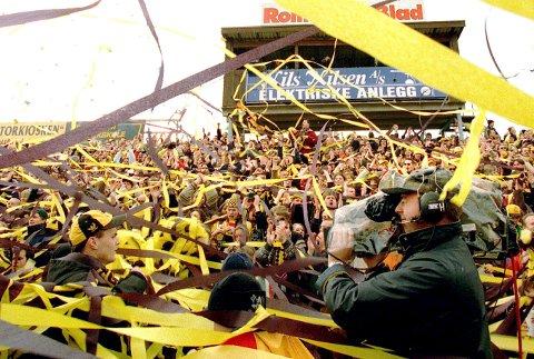 ENGASJEMENT: Den gamle ståtribunen med elleville kanarifans i hatkampen mot RBK i april 1997. André Bergdølmo skulle spille for første gang for Rosenborg på Åråsen, men kom aldri på banen. Arild Myklebust organiserer troppene. FOTO: TOM GUSTAVSEN Bildetekst