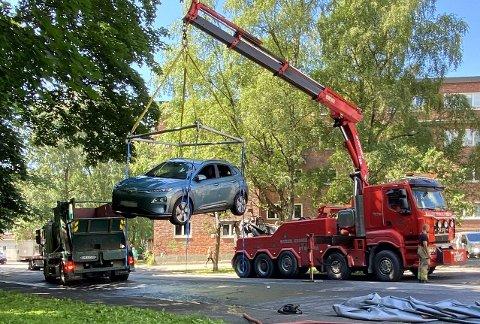 CONTAINER: Her forsøker brannvesenet å senke bilen i en container med vann for å slukke brannen i batteriet.