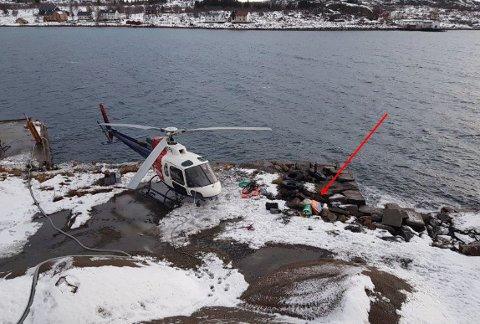 Landingsplassen på kaia. Bildet er tatt innenfor en time etter havariet. Helikopteret står med fronten mot vest. Rød pil viser hvor lastesekken (bigbag) som var fylt med utstyr var plassert. Den fløy opp da helikopteret landet og ble ført inn i hovedrotoren. Den andre samlingen med utstyr og flatpakkede lastesekker, til venstre, nærmere helikopteret, lå i ro.
