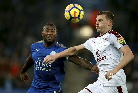 Leicester City's Wes Morgan, left, and Burnley's Chris Wood fight for the ball during the English Premier League soccer match between Leicester City and Burnley FC at the King Power Stadium. Leicester, England. Saturday. Dec. 2, 2017. (Mike Egerton/PA via AP)