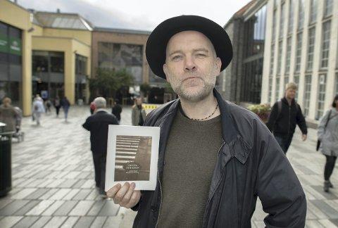 Poeten Henning H. Bergsvåg med den tyske bergensantologien «Hinter dem Regen» i hendene.