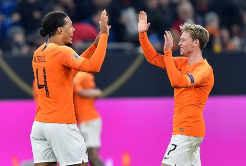 Virgil Van Dijk (t.v.) og Frenkie De Jong feirer etter 2-2-kampen melom Nederland og Tyskland i Gelsenkirchen. Vi tror de nederlandske spillerne kommer til å ha like brede smil etter kampen mot Tyskland i Hamburg. The match ended 2-2. (AP Photo/Martin Meissner)