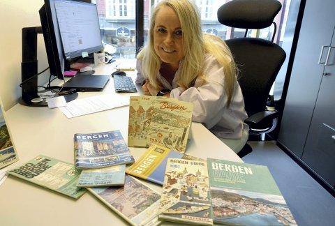 Nærmest for samlerobjekt å regne. Her har Ann Kristin Schei funnet frem bare en del av den store samlingen med tidligere utgaver av Bergen Guide. Noen nesten 70 år gamle. Foto: TOM R. HJERTHOLM