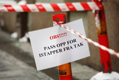 Eit skilt på fortauet åtvarar mot istappar som heng frå eit tak i Oslo. Foto: Erlend Aas / SCANPIX
