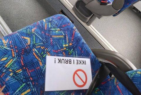 KORONA-TILTAK: På bussen i Hammerfest er slike lapper lagt ut på setet hvor sidemannen skulle vært. Utvilsomt går dette, og manglende turisme og fly nordover utover selskapets økonomi.