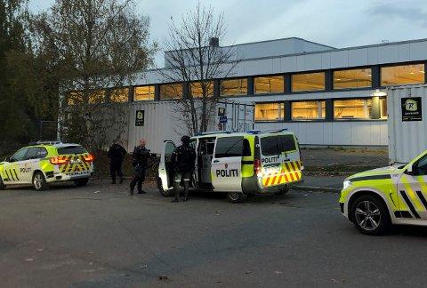 KLARGJØRING: Bevæpnet politi gjorde seg klar rett utenfor Varingens lokaler i Nittedal sentrum mandag i 18-tida før bilene kjørte videre opp Kvernstuveien.