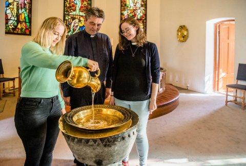 Ingrid Ulvestad fyller vann i døpefonten og sammen med Jan Kay Krystad og Kristin Gulowsen er de tre Ås-prestene klare til å ta imot både påmeldte og de som måtte droppe innom til dåpsseremoni.