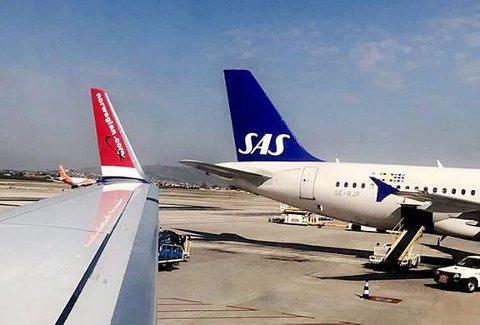 STRANDET: Et SAS-fly og et Norwegian-fly som står strandet på flyplassen på Gran Canaria. Ingen fly har kunnet ta av eller lande der siden lørdag på grunn av sandstorm.