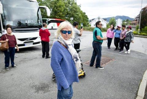 Anna Skutle og flere naboer er irritert over at bussene som kommer med turister står på tomgang mens turistene nyter norsk kulturhistorie.