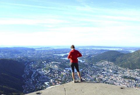 Fra nord til sør er det lagt opp til en 51,5 kilometer langt turtrasé, og står du som denne turgåeren på Ulrikens topp, skimter du Fanafjellet og Krokeide langt der bak ved Fanafjorden. Foto: TOM R. HJERTHOLM