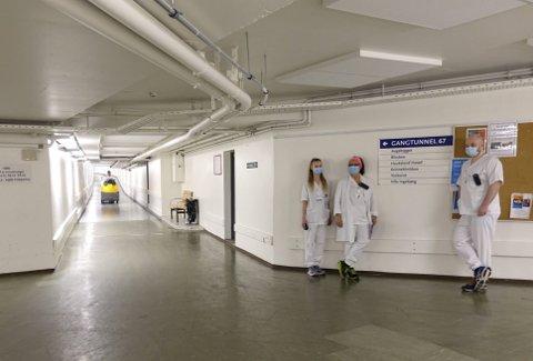 Mariell Hellestveit, Eva Simonsen Hustavenes og Simen Robertsen Rønningen tatt oppstilling ved ett av knutepunktene under Haukeland. Blant portørene benevnes det bare som «Lungekrysset». Til venstre kommer en av kollegaene susende gjennom tunnelen. Foto: TOM R. HJERTHOLM