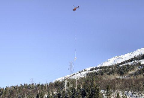 Med mastestål som til sammen veier rundt fjorten tonn, sier det seg selv at en må ha helikopterhjelp. Her er Nord-helikopteret i full sving med ett av de 15 løftene.              Foto: TOM R. HJERTHOLM
