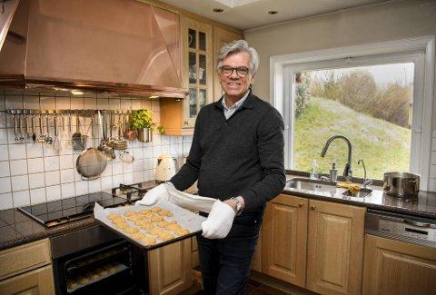 Rune Skjoldal tar et brett med nystekte havrekjeks ut av stekeovnen på kjøkkenet sitt.