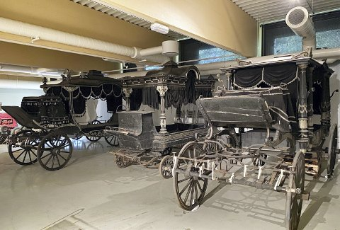 To begravelsesvogner som ble brukt til å frakte rike og betydningsfulle personer på hver side av den litt mindre og høyst enkle utgaven i midten – «fattigmannsvognen» har jernhjul, mens de to andre er utstyrt med gummihjul. Man kan trygt se det var forskjell på fattig og rik. Foto: SØLVI VIK, BYMUSEET