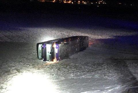 AV VEGEN: En såkalt «dobbeldekker» med nesten 30 passasjerer havnet av vegen og landet på sida etter sterke vindkast ved Skjåk kirke tirsdag morgen.