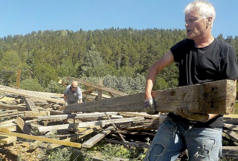 Varm jobb: Hans Andersen (foran) og Vidar Thormodsrud bærer bjelker etter at reisverket til lemmelåven på Berg ved Eidsfoss er tatt ned. Foto: Lars Ivar Hordnes