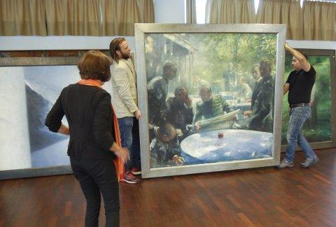 STORE MALERIER: Det er store dimensjoner over mange av maleriene til Vebjørn Sand som stilles ut i Ås kulturhus. Dette maleriet, fra Wannsee-konferansen i Berlin i 1942, er et av mange motiver i serien «Individets valg». Til venstre kulturkonsulent Tone Vik og Aune Sand.