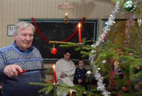 STEMNINGSFULLT: Benny Strand i sving med å tenne levende lys på juletreet. I bakgrunnen spkneprets David Andrè Tys med sønnen Linus Andrè Nyberget Tys.