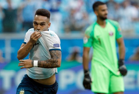 Argentina's Lautaro Martinez, left, celebrates scoring against Qatar during a Copa America Group B soccer match at Arena do Gremio, Porto Alegre, Brazil, Sunday, June 23, 2019. Argentina won 2-0 to reach the Copa America quarterfinals and avoid being eliminated in the group stage of the South American tournament for the first time since 1983. (AP Photo/Victor R. Caivano)