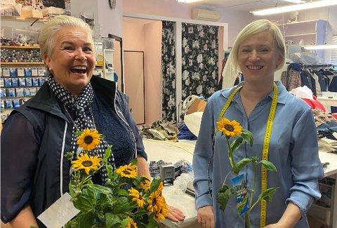 Solveig Albretsen (t.v.) er ute og deler ut solsikker til bedrifter i Solakrossen. Her hos Iwona Maria Misniakiewicz hos Lykkeliten.