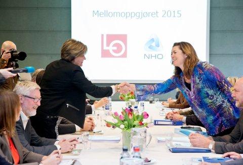 LOs leder Gerd Kristiansen (t.v) og NHOs administrerende direktør Kristin Skogen Lund hilser på hverandre ved forhandlingsstarten for mellomoppgjøret 2015 i Næringslivets Hus i Oslo mandag.