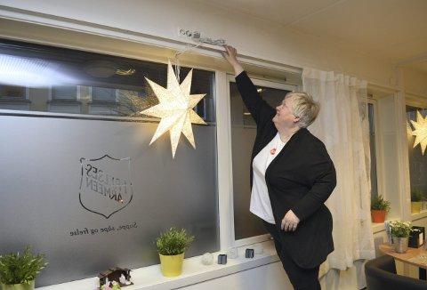Daglig leder på velferdssenteret i Hans Hauge gate gjør klar for litt førjulstid. Her kommer den siste av julestjernene på plass i vinduet. (Foto: TOM R. HJERTHOLM)
