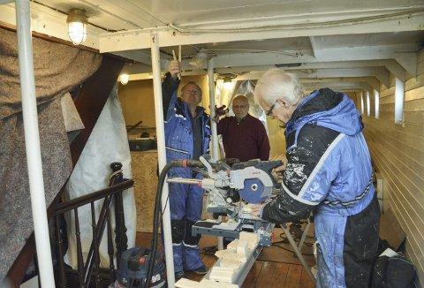 Her er Inge Halland (t.v.), Arne Sundal og Kjell Ågotnes under dekk, hvor de to kjeledresskledde holder på å kle inn dekksbjelkene.