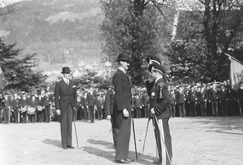 Det tette forholdet mellom Dræggens Buekorps og Bergenhus festning, ga seg i 1931 utslag i at selveste Kong Haakon kom for å inspisere buekorpset ved 75-årsjubileet. Dræggegutt og lokalhistoriker Jo Gjerstad tar for seg nettopp forholdet med buekorps og festningen i aprilforedraget.