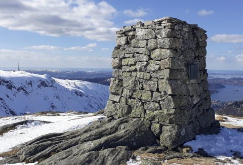 Dette er steinvarden med det lange navnet. Til venstre skimter vi Ulriksmasten, mens det er byen og Byfjorden til høyre for varden.  (Foto: BERGEN OG HORDALAND TURLAG)