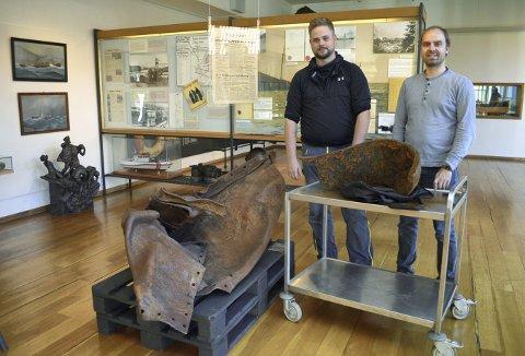 Marinarkeologene Tord K. Karlsen (t.v.) og Eirik Søyland ved Bergens Sjøfartsmuseum. Her med den forvridde delen museet har etter «Voordbode»-eksplosjonen på Festningskaien 20. april 1944. Delen til høyre kommer fra bunnen av Munkebotsvatnet. (Foto: TOM R. HJERTHOLM)