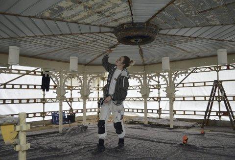 Her er det Irmelin Danielsen Urdal som sørger for at selve himlingen av tre igjen skal skinne i linoljemalingen. Alt arbeide med Musikkpaviljongen er i rute og 12. mai skal alt være ferdig. (Foto: TOM R. HJERTHOLM)