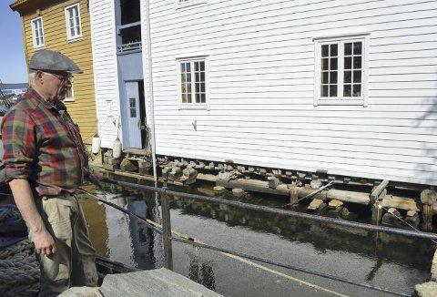John Audun Hauge studerer nederste del på sjøboden han har hevet. Det han fikk lagt inn under, er nå under vannlinjen. (Foto: TOM R. HJERTHOLM)