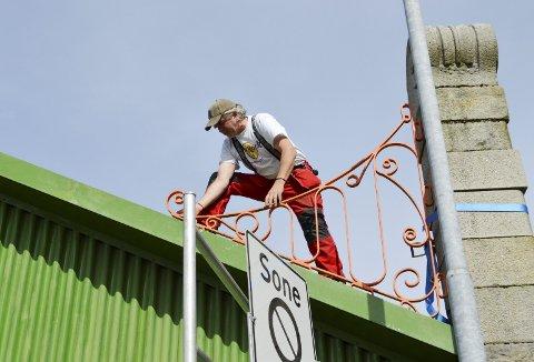 Roger Iversen har kommet seg på taket av Skur 11 der han skal måle ut festepunkter for det smijernsornamentet. (Foto: TOM R. HJERTHOLM)