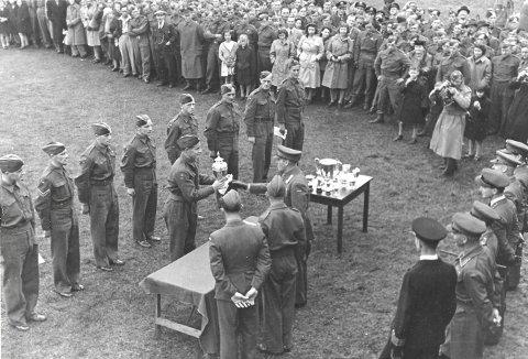I morgen er det nøyaktig 75 år siden den norske forsvarssjefen, Kronprins Olav, delte ut pokalen til vinnerlaget i skotske St. Andrews. Her mottar bergenser Karl Sebak pokalen under den høytidelige stunden. Det var fortsatt krig hjemme i Norge. ( Foto:  PRIVAT