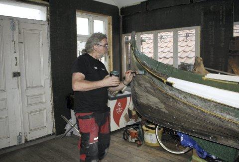 Nordlandsbåten som Roger Iversen her holder å male, dukket helt tilfeldig opp. – Jeg ble spurt om jeg kunne ta hånd om den, og har nå gjort det som måtte gjøres. Når den er helt ferdig, er tanken at den skal bli en julepresang til Bergen Havn som vil ha den utstilt i terminalbygget til Hurtigruten. Foto: TOM R. HJERTHOLM