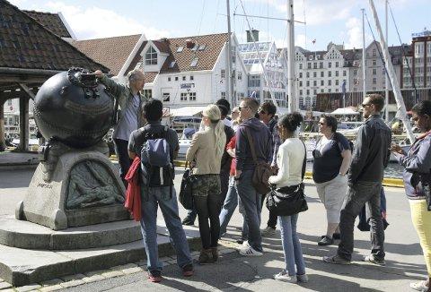 Byvandringer er noe Bård Gram Økland har holdt på med i flere år og byvandringer har vært populære også i sommer. Dette er fra en vandring med turister sommeren 2013. Foto: TOM R. HJERTHOLM