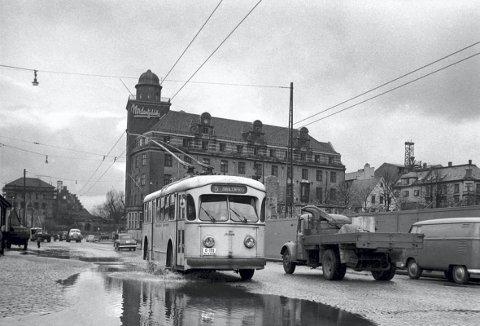 De første trolleybussene rullet over Bryggen på vei fra Mulen til Møhlenpris. Dette bildet viser en av bussene på slutten av 1950-tallet med Nordenfjeldske-bygget i bakgrunnen.